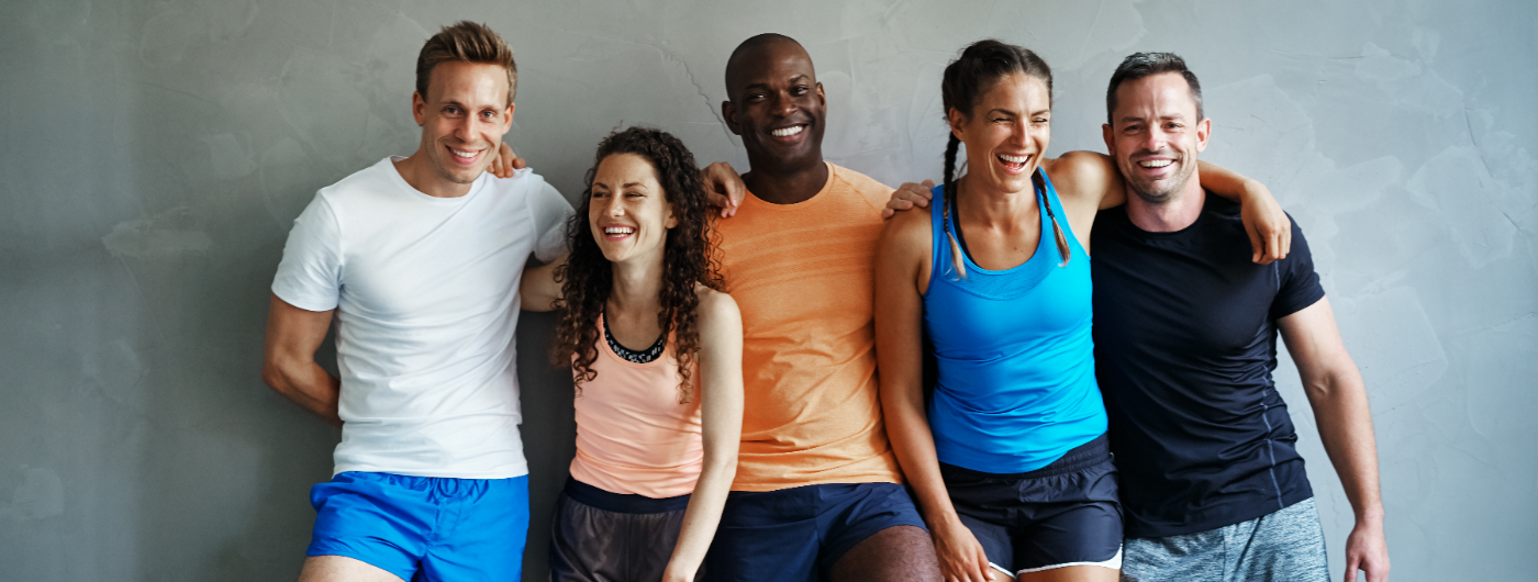 Diverse young friends in sportswear laughing together at the gym